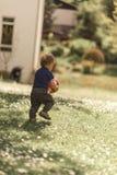 Kleinkind, das einen Ball trägt Stockfotos