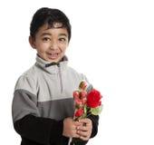 Kleinkind, das einen roten Rosen-und Süßigkeit-Blumenstrauß anhält Stockfoto