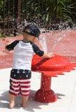 Kleinkind, das in etwas Wasser spielt Lizenzfreies Stockbild