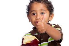 Kleinkind, das Frucht isst und Daumen aufgibt Stockfotografie