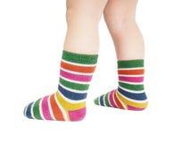 Kleinkind, das in gestreiften Socken und in den bloßen Beinen steht Stockfotos