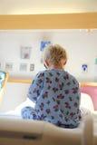 Kleinkind, das im Krankenhaus-Bett sitzt Stockfotografie