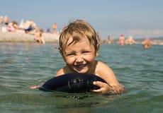 Kleinkind, das im Meer auf aufblasbarer Auflage badet Lizenzfreie Stockfotografie