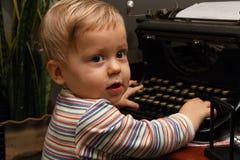 Kleinkind, das mit alter schwarzer Schreibmaschine spielt Stockbilder