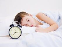 Kleinkind, das mit Borduhr nahe seinem Kopf schläft Lizenzfreie Stockfotografie