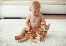 Kleinkind, das mit Katze spielt lizenzfreie stockbilder