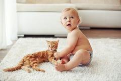 Kleinkind, das mit Katze spielt stockfotos