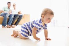 Kleinkind, das mit Muttergesellschaftn im Hintergrund kriecht Lizenzfreies Stockfoto