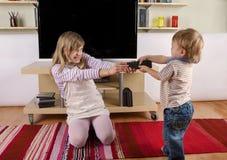 Kleinkind, das mit seiner Schwester über der Fernbedienung kämpft Stockbilder
