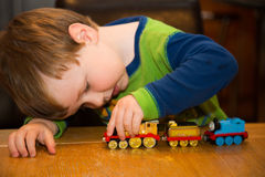 Kleinkind, das mit Spielzeugzug spielt stockfotos
