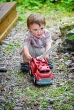 Kleinkind, das mit Toy Fire Truck Outside - Reihe 1 spielt Stockbild
