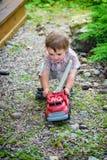 Kleinkind, das mit Toy Fire Truck Outside - Reihe 3 spielt Stockfotografie