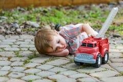 Kleinkind, das mit Toy Fire Truck Outside - Reihe 5 spielt lizenzfreie stockfotos