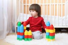 Kleinkind, das Plastikblöcke spielt Stockfotografie