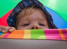Kleinkind, das Playfully über Stuhl schaut Lizenzfreies Stockbild
