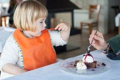 Kleinkind, das Schokoladenkuchen mit Frau isst Stockfotografie