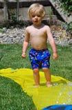 Kleinkind, das vorsichtig auf Water-slide geht lizenzfreies stockbild