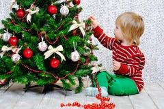 Kleinkind, das Weihnachtsbaum verziert Lizenzfreie Stockbilder