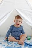 Kleinkind des kleinen Jungen in einem gestreiften Trägershirt, das im Tipi sitzt stockfoto