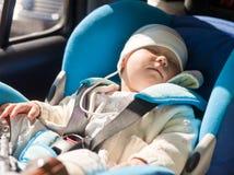 Kleinkind in einem Autositz Stockfotos