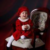 Kleinkind in einem Weihnachtskleid Stockbild