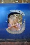 Kleinkind in einer zerbrochenen Fensterscheibe Lizenzfreie Stockfotos