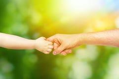 Kleinkind hält die Hand seines Vaters Stockbild