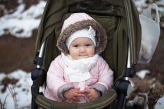 Kleinkind im Spaziergänger in der Jacke, im grauen Schal und im Fedorahut Lizenzfreie Stockbilder