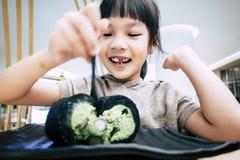 Kleinkind isst grüner Tee matcha Kuchenrolle Stockfotografie