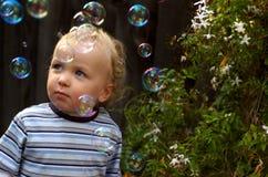 Kleinkind-Junge, der mit Luftblasen spielt Stockbilder