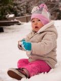 Kleinkind-Kleinkind, das im Schnee sitzt Stockbild