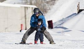 Kleinkind lernt, mit Vati Ski zu fahren Sicher angekleidet stockbild