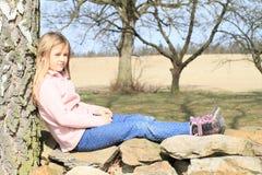 Kleinkind - Mädchen, das auf Steinen sitzt Stockfotos