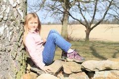 Kleinkind - Mädchen, das auf Steinen sitzt Lizenzfreie Stockbilder