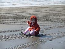 Kleinkind-Mädchen, das im Schlamm sitzt Lizenzfreie Stockfotografie