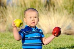 Kleinkind mit Äpfeln Stockfoto