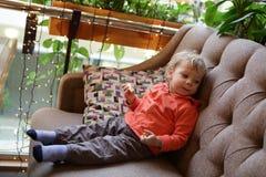 Kleinkind mit Apfel auf Sofa Stockbilder