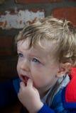 Kleinkind mit dem Finger in seinem Mund Stockbilder