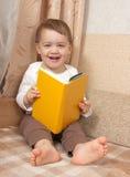 Kleinkind mit einem Buch auf Sofa Stockfotos