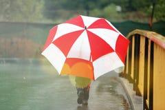 Kleinkind mit einem großen Regenschirm Stockfotos