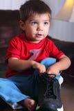 Kleinkind mit großem Schuh des Vatis Stockfotos