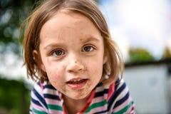 Kleinkind mit schmutzigem Gesicht vom Spielen draußen im Schmutz und stockfotografie