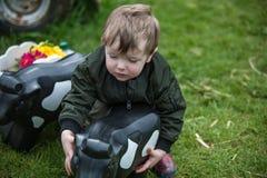 Kleinkind mit Spielzeugkuh stockbilder
