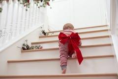 Kleinkind mit Weihnachtsbogen auf Treppe in den Pyjamas Lizenzfreie Stockfotografie
