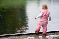 Kleinkind neben Enteteich Stockfotos