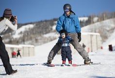 Kleinkind schreit mit Freude, wie er lernt, mit Vati Ski zu fahren, während Mutter ein Foto macht Stockbilder