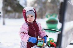 Kleinkind spielt mit Spielwaren im Winter im Park stockfoto