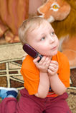 Kleinkind spricht über Handy Stockfotos