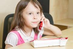 Kleinkind am Telefon mit den geschürzten Lippen Stockbild