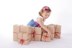 Kleinkind und ein Stapel Geschenke Stockfoto